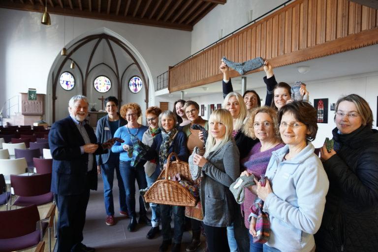 Ehrenamt schätzt Hauptamt: Foto der Überreichung von selbstgestrickten Socken mit den hauptamtlichen Mitarbeitenden im Elisabethen-Hospiz.